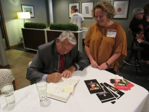 Governor Thompson writes a heartwarming message at his Book signing event